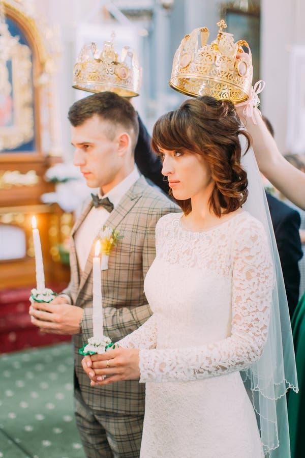 Das vertikale Seitenporträt des Jungvermähltenhändchenhaltens bei der Stellung unter den Kronen während der Hochzeitszeremonie stockfotografie
