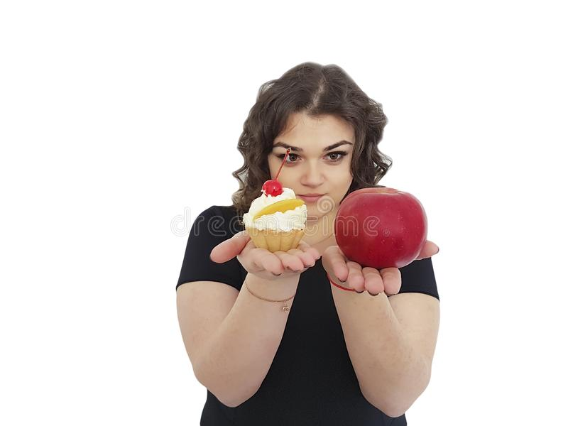 Das volle Mädchen, das Kuchen wählen und ein Apfel lokalisiertes Dilemma widerstehen lizenzfreie stockbilder