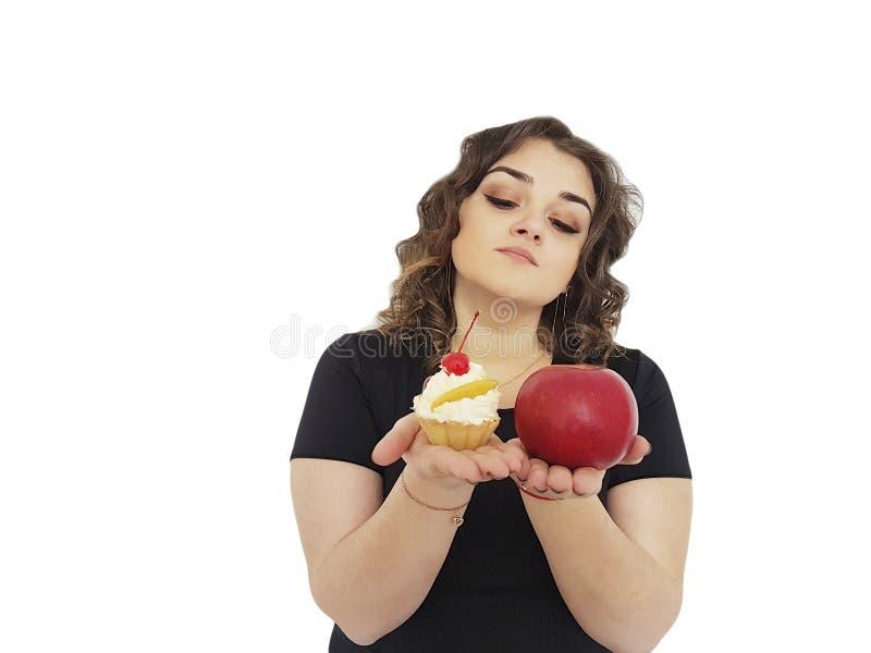 Das volle Mädchen, das nährenden Kuchen wählen und ein Apfel lokalisiertes Dilemma widerstehen stockfoto
