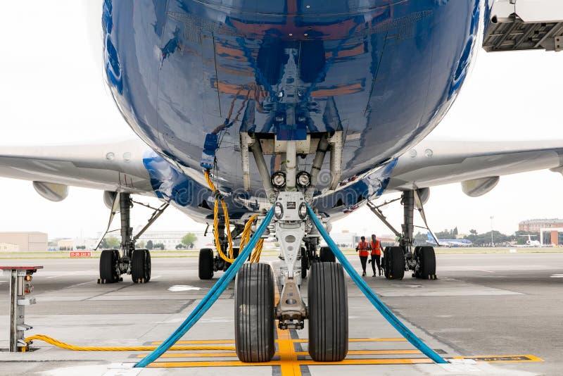 Das vordere Fahrwerk der Flugzeuge, die auf der Brennstoffaufnahme am Flughafen stehen stockbilder