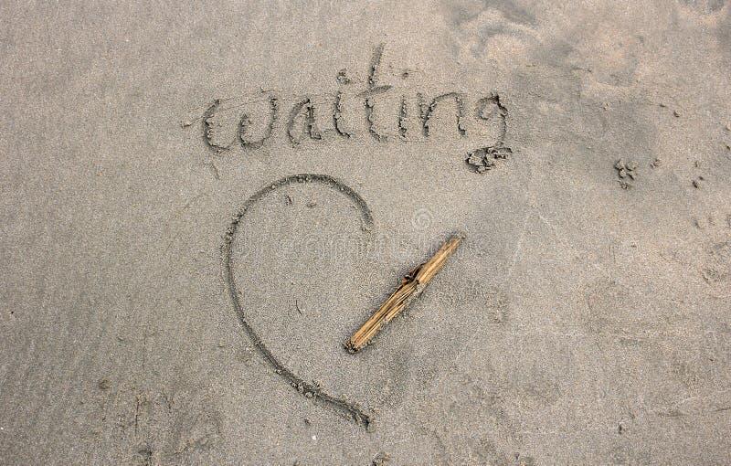 Das Wartewort auf dem Sand vom Strand lizenzfreies stockfoto