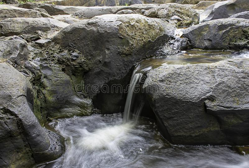 Das Wasser, das ?ber Felsen und B?ume hinunter einen Wasserfall an Wasserfall Khao Ito, Prachin Buri in Thailand flie?t lizenzfreies stockbild
