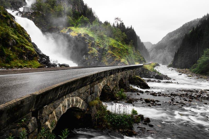 Das Wasser eines Wasserfalls fließt in ein grünes Tal auf zwei unterschiedlichen Arten Der Boden ist felsig und von Steinen und v stockbilder