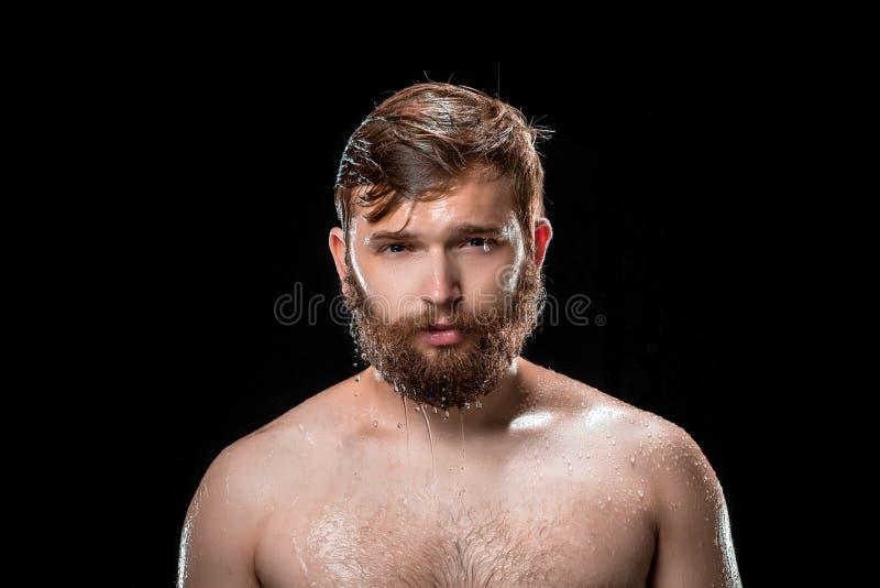 Das Wasserspritzen auf männlichem Gesicht stockfotografie