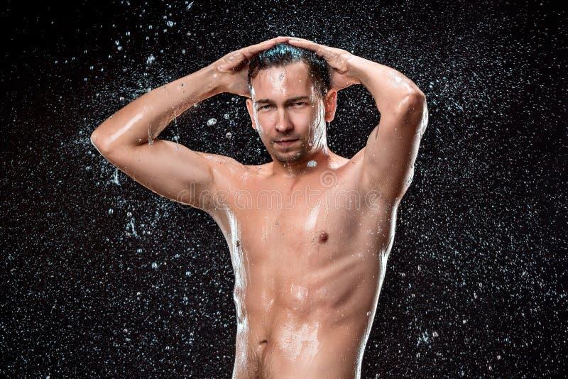 Das Wasserspritzen auf männlichem Gesicht lizenzfreies stockfoto