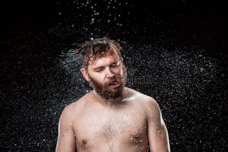 Das Wasserspritzen auf männlichem Gesicht lizenzfreie stockfotos