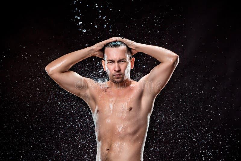 Das Wasserspritzen auf männlichem Gesicht lizenzfreies stockbild