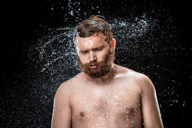 Das Wasserspritzen auf männlichem Gesicht stockfotos