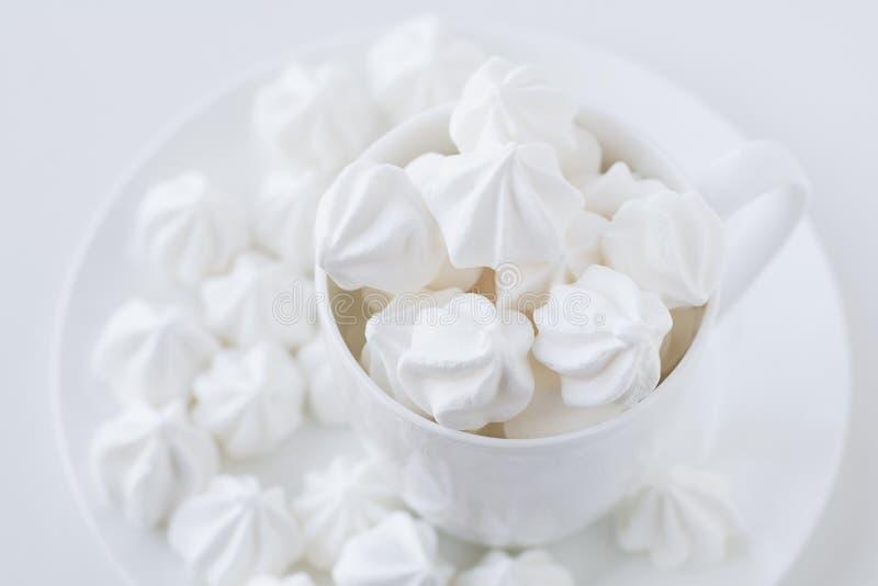 Das weiße merengue in der weißen Teeschale auf weißem Hintergrund stockfotos