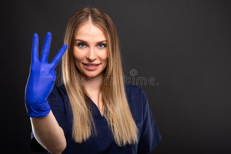 Das weibliche Zahnarzttragen scheuert das Darstellen, Nr. drei zeigend lizenzfreie stockfotografie