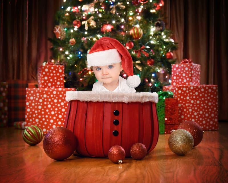 Das Weihnachtsbaby, das durch Baum sitzt, beleuchtet zu Hause lizenzfreies stockfoto