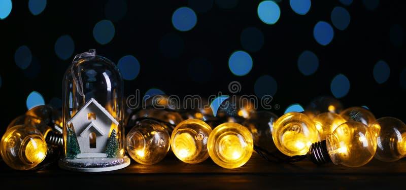 Das Weihnachtsdekorations- Weiße Haus innerhalb des Glases zwischen Lichtern Bul lizenzfreie stockfotos