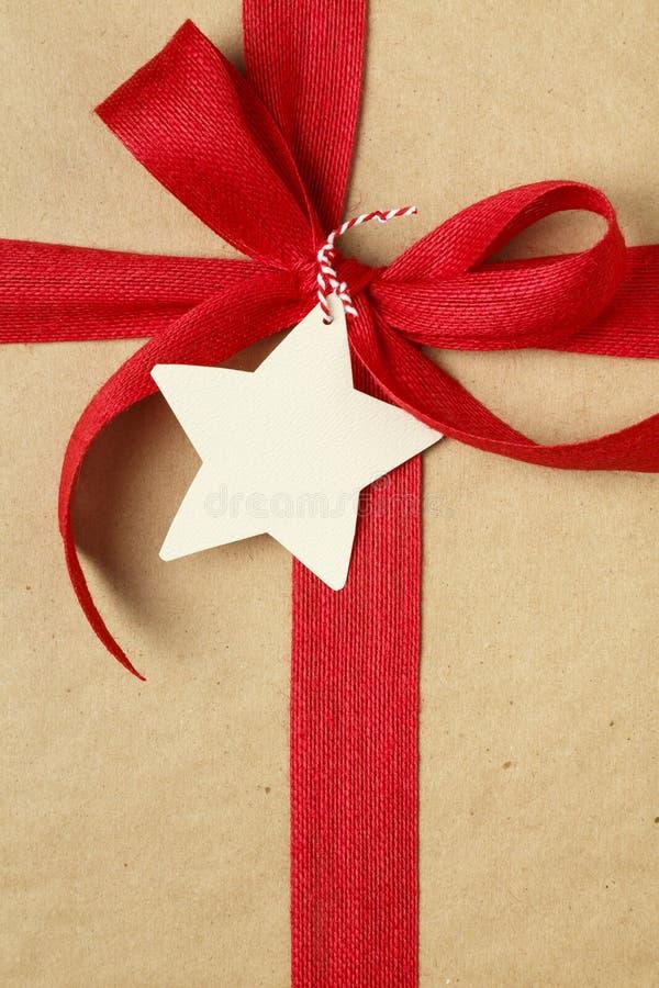 Das Weihnachtsgeschenk, das mit rotem Bogen vorhanden sind und das leere Geschenk etikettieren Einfacher, aufbereiteter Kraftpapi stockbilder