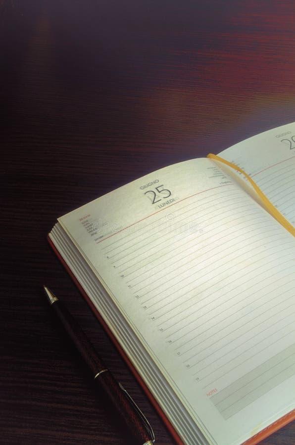 Das Weinlesebild eines Notizbuches mit einem Stift auf einer Tabelle lizenzfreies stockfoto