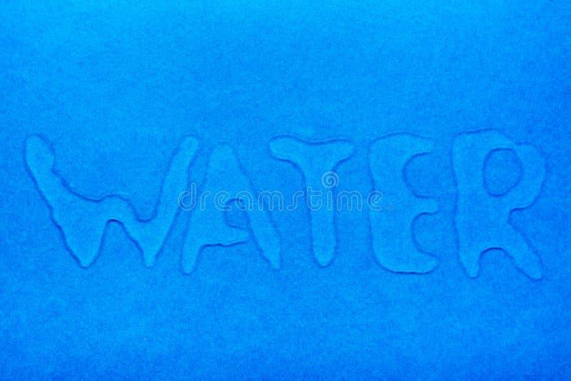 Das Wort 'Wasser 'wird mit Wassertröpfchen auf eine blaue glatte Oberfläche geschrieben lizenzfreies stockbild