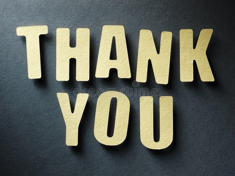 Das Wort danken Ihnen auf Papierhintergrund stockbild
