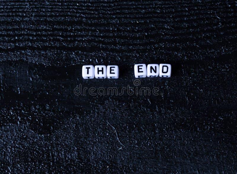 Das Wort ` das Ende ` wird von den Würfeln auf einem schwarzen hölzernen Hintergrund gemacht Schwarzer Hintergrund lizenzfreies stockfoto
