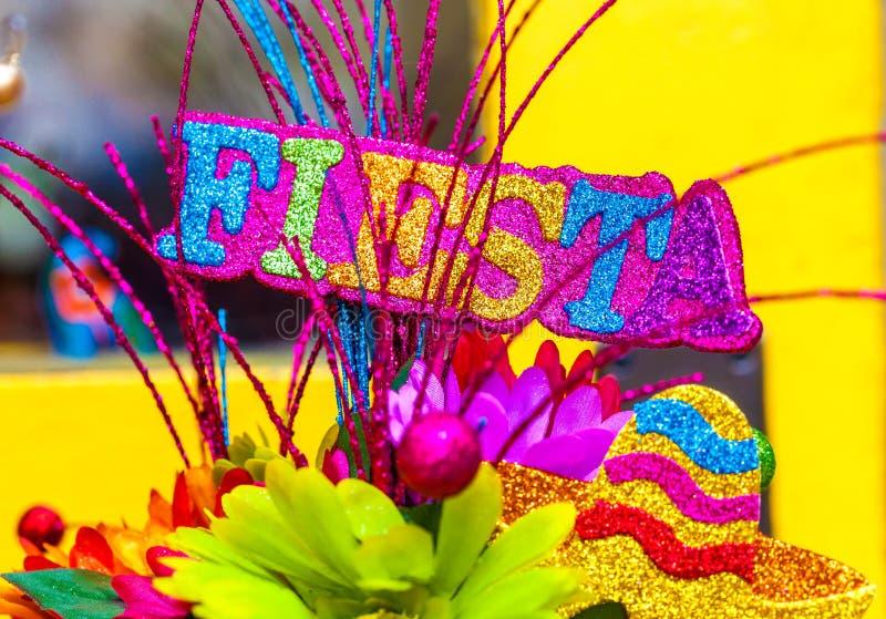 Das Wort ` Fiesta ` geschrieben in bunte Funkelnbuchstaben mit Sombrero und Papierblumen stockbilder