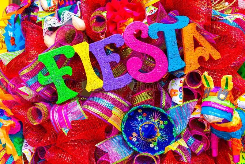 Das Wort ` Fiesta ` geschrieben in bunte Schaumbuchstaben auf den mehrfarbigen Brei verziert mit Funkeln und kleinem Sombrero lizenzfreies stockbild