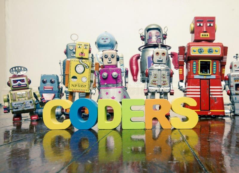Das Wort KODIERER mit hölzernen Buchstaben und Retro- Spielzeugrobotern auf lizenzfreie stockfotografie