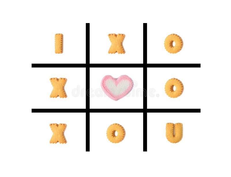 Das Wort LIEBE ICH U im Tic Tac Toe Game, der mit Alphabet gemacht wird, formte Plätzchen und eine geformte Eibischsüßigkeit des  lizenzfreie abbildung