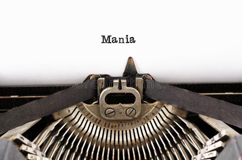 Das Wort ` Manie ` von einer Schreibmaschine auf Weiß lizenzfreie stockbilder