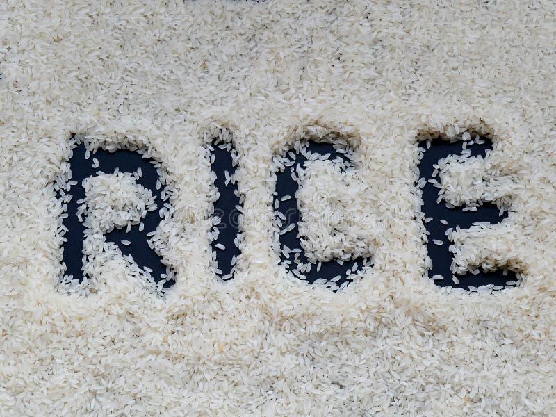Das Wort ` Reis ` geschrieben mit einem Finger auf eine Schicht weißen rohen Reis, der auf einen dunklen Hintergrund liegt stockfoto
