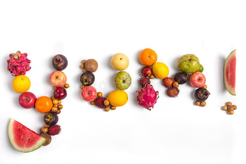 Das Wort Yum, ausgeschrieben von den St?cken Frucht mit wei?em Hintergrund lizenzfreies stockfoto