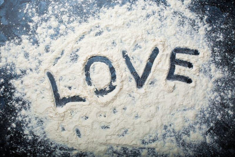 Das Wort zeichnend, lieben Sie auf einem zerstreuten Mehl auf einem dunklen Hintergrund lizenzfreies stockbild