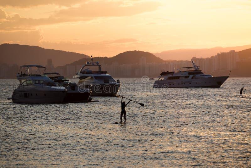 Das Yacht- und Leute?ben stehen oben Paddel, w?hrend des Sonnenuntergangs, in Guaruja, Brasilien lizenzfreies stockbild