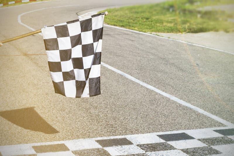 Das Ziellinie- und Zielflaggelaufen beenden Sie das Rennen stockfotos