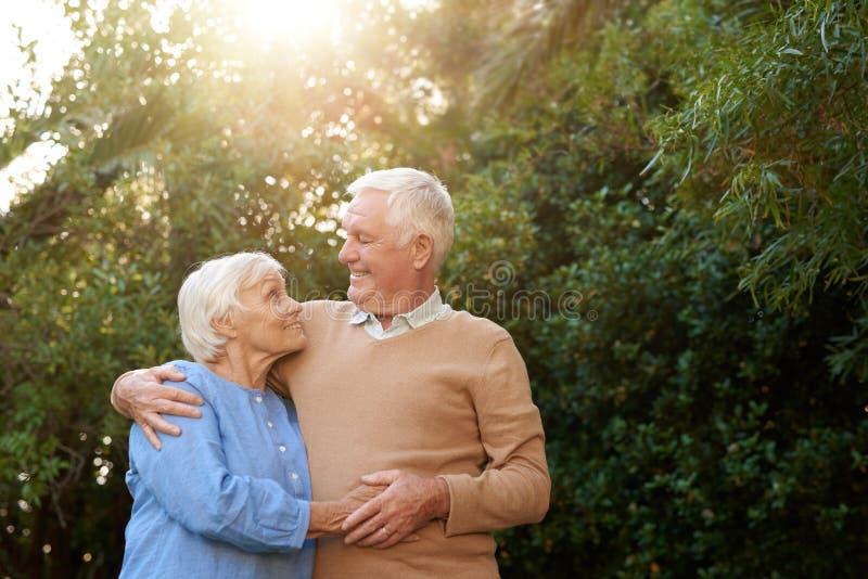 Das zufriedene ältere Paar, das in einander ` s steht, bewaffnet draußen stockbild