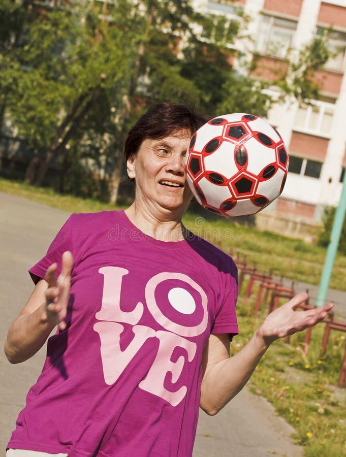 Das Zur Schau tragen einer alten Frau versucht enthusiastisch, den Ball zu fangen, der zu ihr geworfen wird Spielen des Fußballs stockfotos