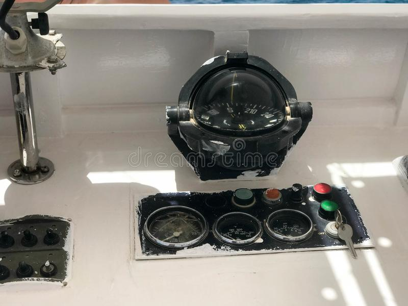 The dashboard is on a boat, ship, maritime transport with a large glass round black compass, a tachometer, a speedometer, an ignit stock photos