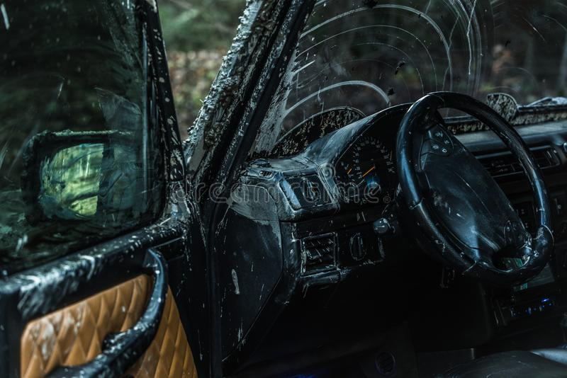 Dashboard of car after offroad race. SUV with open door. Dashboard of car after offroad race. Fall forest is in front of car. Dashboard and steering wheel royalty free stock photos