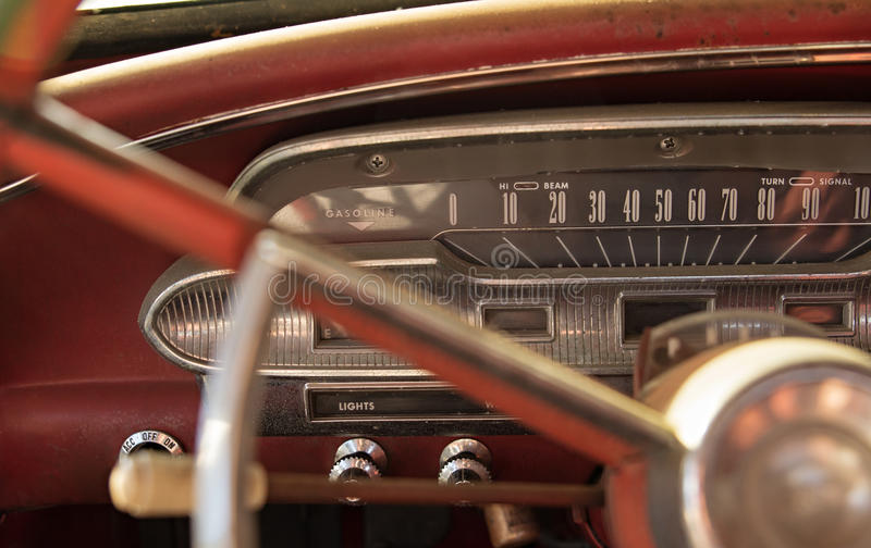 Dashboard of a vintage car. View of dashboard including speedometer, gauges, steering wheel, and switches on a red vintage car royalty free stock images