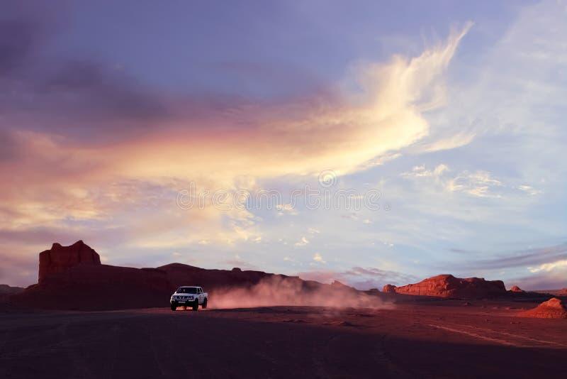 Dashte Lut woestijn in Iran De auto in motie op de achtergrond van de zonsondergang Wilde aard van Perzië royalty-vrije stock fotografie