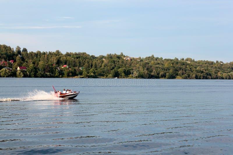 Dat ensolarado no rio Os amantes montam em um barco em um lago durante um por do sol bonito Mulher feliz e homem dos pares que re fotografia de stock