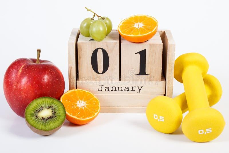 Data 1° gennaio sul calendario del cubo, sui frutti e sulle teste di legno, nuovi anni di concetto di risoluzioni immagini stock