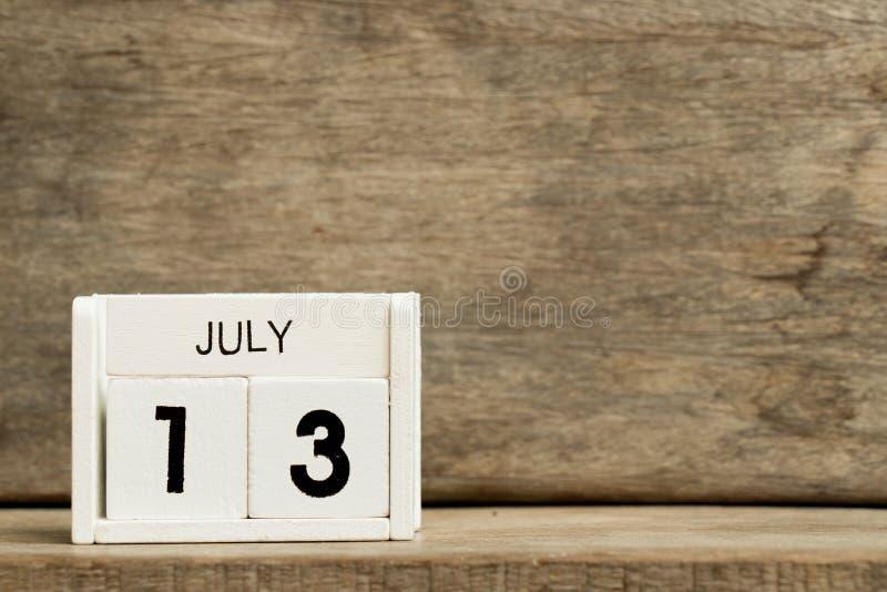 Data atual branca 13 do calendário de bloco e mês julho na madeira para trás fotografia de stock
