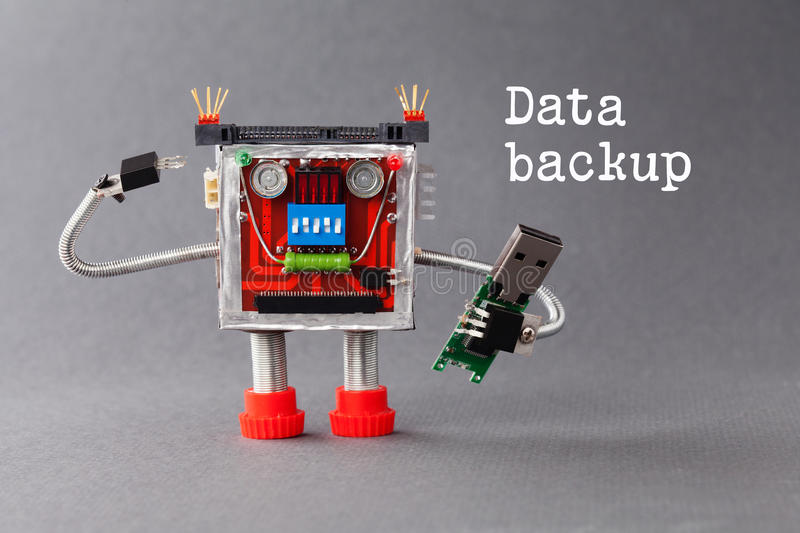 Data backup concept. Robotic character with portable usb device flash stick. Macro view, gray background. Backup information concept. Robot with portable usb royalty free stock photography
