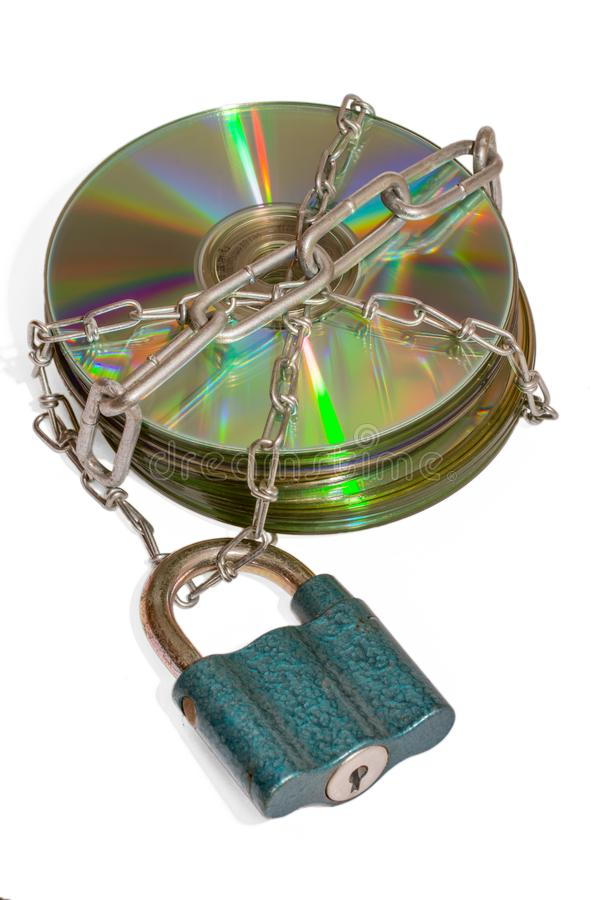 Data backup shows with included disk. A stack of CDs surrounded by metal chains secured with a lock against a white background royalty free stock photo