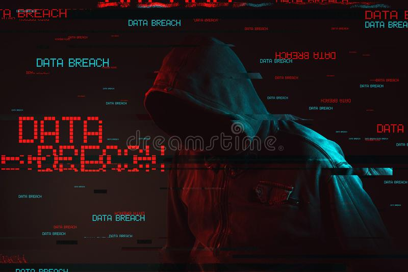 Data breach concept with faceless hooded male person. Low key red and blue lit image and digital glitch effect stock photography
