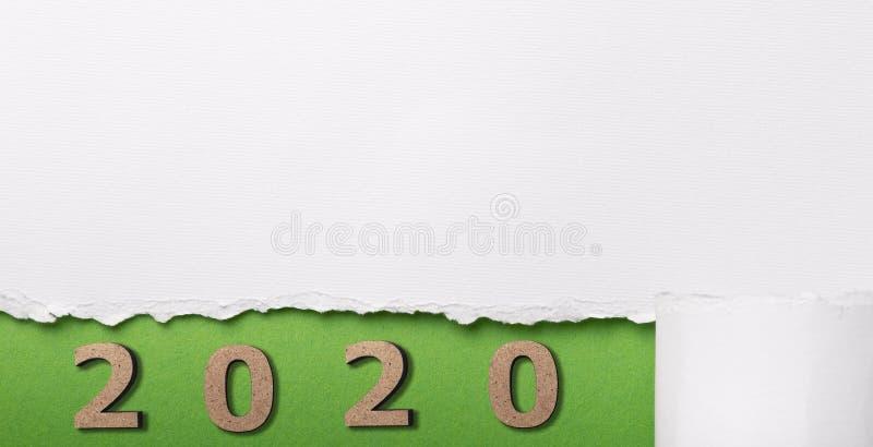 data con figura in legno 2020 sotto una striscia di cartone bianco strappata, numeri in foro verde di carta strappata, concetto d immagini stock