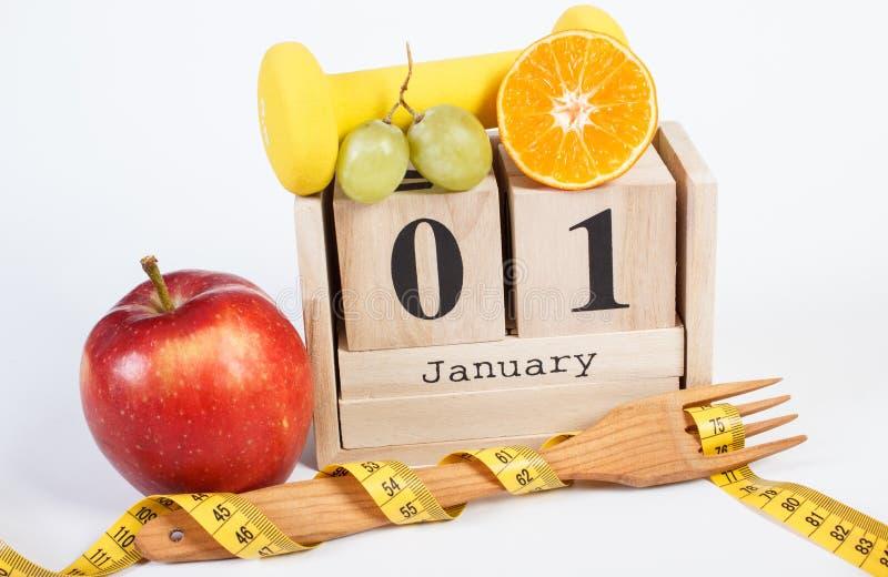 Data del 1° gennaio sul calendario del cubo, sui frutti, sulle teste di legno e sulla misura di nastro, nuovi anni di risoluzioni immagini stock libere da diritti