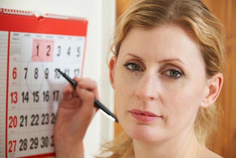 Data di circonduzione preoccupata della donna sul calendario immagine stock libera da diritti