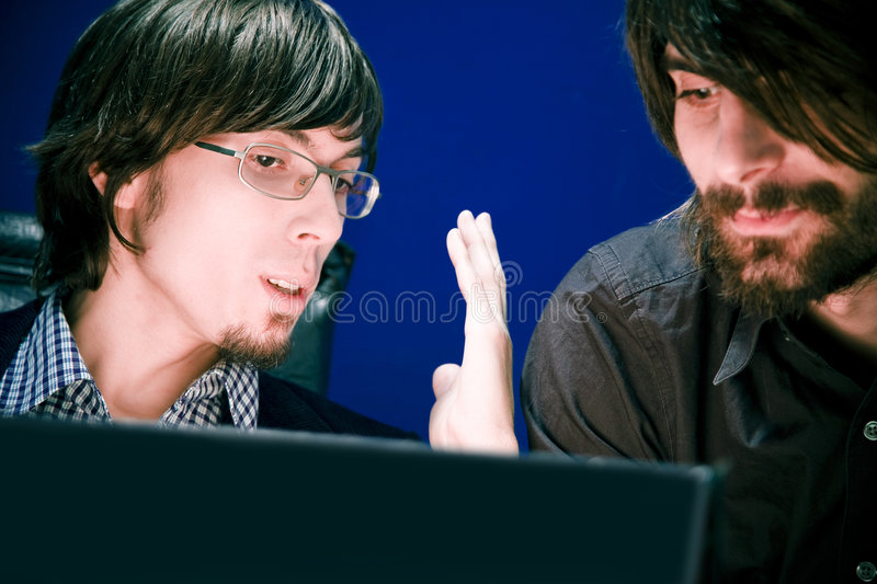 Data Discussion. Two young men having a discussion over information displayed on a laptop in front of them royalty free stock photo