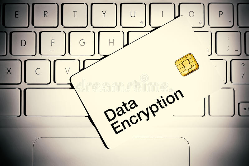 Data Encryption Concept. Smart card on a keyboard of white laptop computer stock photos