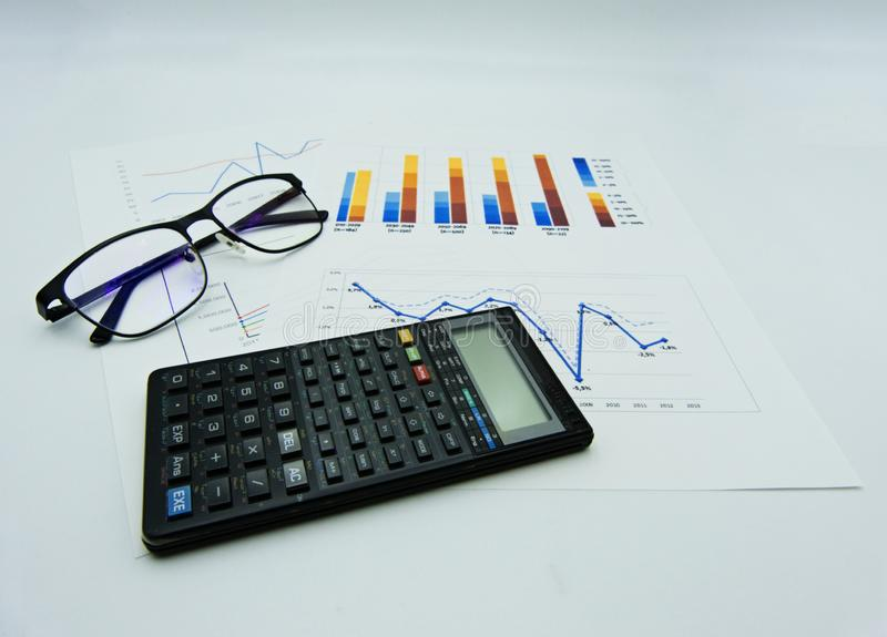 Data graphs and diagrams, glasses and calculator, white background royalty free stock images