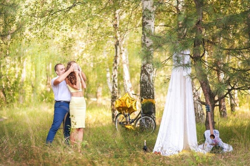A data no homem da floresta A conduz uma mulher com olhos fechados a um local do piquenique com uma barraca branca da cortina de  imagens de stock royalty free